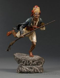 Bergman Cold Painted Bronze Figure of an Arab Warrior, early 20th century, the man modeled running forward in attack, wearing red turban and striped head wrap and sash, holding a long rifle in one hand, on rough hewn black stone base, mold.