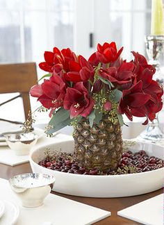 Pineapple Centerpiece ~ Slice off the top of the pineapple. Scoop out the delicious contents. Place flowers in center.  Add eucalyptus, or any natural green around the flowers. Surround your centerpiece with cranberries, and you have a great holiday centerpiece! Don't forget to put water in this natural vase - click for more