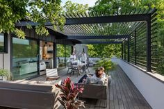 Custom-made steel and glass sliding doors open the living space of this modern house to a large roof terrace creates an indoor/outdoor living environment. #RoofTerrace #ModernPergola #OutdoorSpace