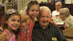 """USS Indianapolis survivor Verlin """"Buzz"""" Fortin poses with his great-granddaughters at the Golden Oaks Senior Living Community in Yucaipa, Ca..."""