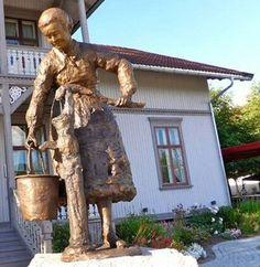 Siden 2007 har Lillestrøm har «Den stolte Sagarbeideren» ønsket tilreisende med tog til Lillestrøm velkommen. Forankret i byes historie, og til heder og ære for alle de som jobbet på sagbrukene.   Men der var selvfølgelig også kvinner. Sterke, flotte, utholdende kvinner som også fortjener sin plass i byens historie. «Konen ved vannposten» er til heder og ære for disse kvinnene, og er som «Den stolte Sagarbeideren» et verk av Tore Bjørn Skjølsvik Kunstverket ble gitt av Lillestrømfondet