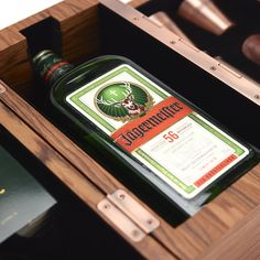 The pack comprises a wooden, copper-hinged box, emblazoned with the Jägermeister branding and fastened with an orange leather strap. Upon opening, the box smoothly expands, folding out into three separate compartments. A bottle of Jägermeister sits in the centre; the other recesses contain two copper shot glasses, a Boker pocket knife sheathed in leather, a vintage retractable telescope, an embossed pocket watch bearing the famous Jägermeister stag, and a set of 56 unique postcards.