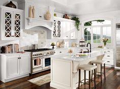 dark hardwood flooring, framed white kitchen cabinets, light colored kitchen counter tops