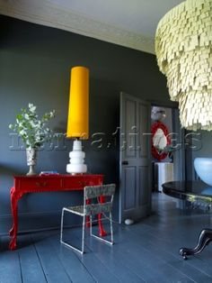 Mid blue grey decorated room with bright red painted console table and yellow lamp and chandelier on