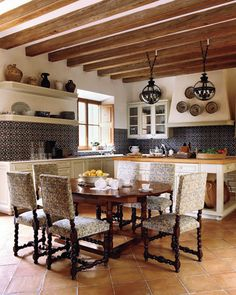 Terra Cotta floor, spanish time, dark metal pendant lamps, and a butcher block counter. This kitchen has tied it all together. Close paint color: Dollop of cream by Sherwin Williams.