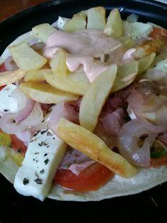 Piadina con pomodoro, tuma, prosciutto cotto, cipolla, patatine fritte e salsa rosa.