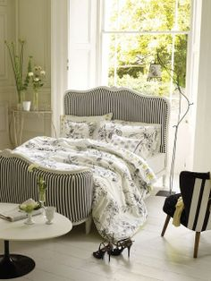 I love the curvy footboard on this bed. Also dig the stripes but not sure I could live with those for long.