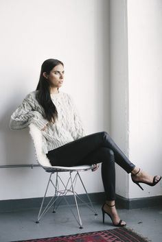 Gray cable-knit alpaca sweater with black leather leggings.