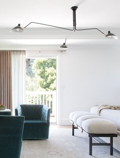 IDF Studio - Show-stopping mid-century chandelier and teal chair in luxurious master bedroom.