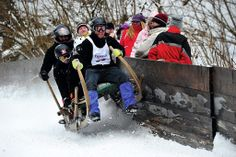 The courageous pilots speed down the slope with more than 100 km per hour. Four persons occupy one wooden sledge. http://www.edelweisslodgeandresort.com/area-info/special-events/traditional-sled-race