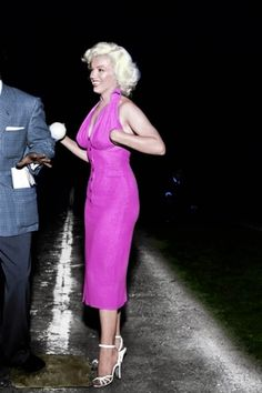 Marilyn Monroe 1953 bombshell, wears traffic-purple fitted sleeveless dress, with long v-neck and white ankle strap heels. She really understood fashion and how to put her image together.