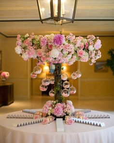 Escort cards surrounded a pink floral arrangement embellished with glass orbs. #WeddingDecor Photography: Marianne Lozano Photography. Read More: http://www.insideweddings.com/weddings/pink-white-wedding-with-ombre-details-at-montage-laguna-beach/686/