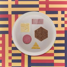 """Jamie Brown & Luke Kirwan, depicts 20th century art and design movements in food. Brown:  """"There are few things that rival my insatiable hunger for color and pattern, my appetite for food is one.The concept was born to represent design movements of the 20th century through specially arranged plates of appropriate foods, finished with hand cut patterned paper table cloth backgrounds. Bauhaus, a simple selection of Bavarian cold meats and cheeses, rye bread and a touch of mustard. - The Gourmand"""
