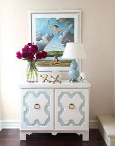Make It Personal: A former ballerina, Warner fell for Rafal Olbinski's print of a dancer and hung it in the living room above a Hollywood Regency-style cabinet, opposite the sofa. The lamp is from Restoration Hardware. Giant jacks are a flea market find.