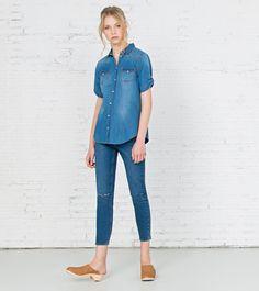 Camisa denim,de manga corta con opción de roll up, con dos bolsillos delanteros y con cierre de botones de presión.
