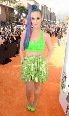 "Katy Perry in neon green slime bra-like top at the 2012 Nickelodeon Kids' Choice Awards. She paired the outfit with matching peep toe heels, purple and blue ponytail, and bublegum lips. And, according to the article, ""pulls off the fun, eclectic look to perfection."""
