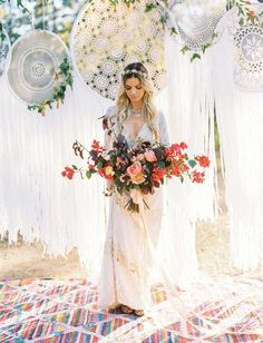 Palm Springs meets Bay Area. Bohemian bride holding red cascading flower bouquet. Perfect elegant boho wedding