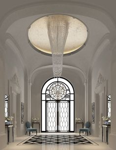 Spectacular white foyer with marble floors and gorgeous chandelier.