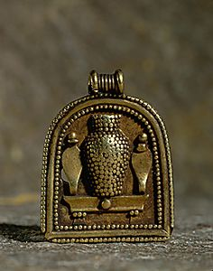 "PHOENICIAN JEWELRY 6TH BCE  Shrine pendant with ""bottle idol"" and Uraei. From Carthage, Tunisia, 7th-6th BCE Silver and gold, granulation, lamination, filigree ."