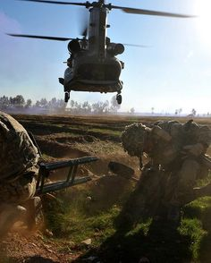 A Chinook flies in low over the heads of Royal Marines from Alpha Company, 40 Commando Royal Marines during Op DAAS 7B.
