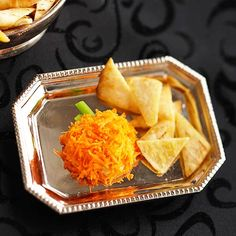 Hummus Pumpkin Halloween Food: Sprinkle grated carrot over  a mound of hummus. Use a celery stick for step.