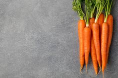 fresh carrots bunch on a grey stone background copy space