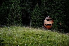 In the woods of Malborghetto Valbruna in the Italian Dolomite commune of Tarvisio is a pair of egg-shaped tree houses that appear to hover in midair, like fruit of the forests.