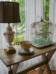 I like this rustic table in front of the window and bottles in the bird cage with bitter sweet. by Chateau Chic