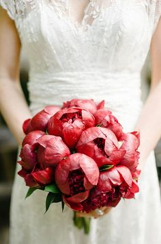 The round shape of partially opened red peonies gives this bouquet a dramatic shape and texture.