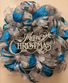 Silver & blue deco mesh wreath w/4 different ribbons accented w/blue ornaments and Merry Christmas sign.