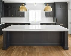 "Black Kitchen Cabinets with White Quartz Countertop, White Oak Hardwood Floor, Brass accents and white subway tile with dark grout. Dark inset cabinets bring a modern feel to this classic kitchen. The overall size of the kitchen is 21'6"" wide by 13'6"" deep. The kitchen island is roughly 11' wide by 4'6"" deep. Kitchen lighting is Eugene Large Pendant - Hand-Rubbed Antique Brass from Circa Lighting. Black Kitchen Cabinets with White Quartz Countertop, White Oak Hardwood Floor, Brass accents…"