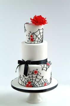 Elegant Halloween cake in white, black and red with piped spiderweb lace and statement red flower.