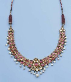 an indian gold necklace set with pink tourmalines. The half-moon shaped necklace consists of a double row of teardrop-shaped beads set with pink tourmaline, suspending with pearl beads, the reverse enamelled with red, green and white flower heads