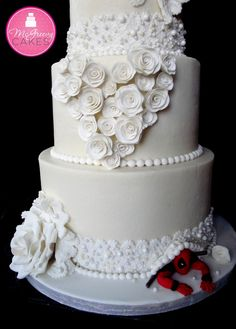 All edible hand made roses, pearl encrusted lace, and rosettes. The rosettes in the shape of a heart was inspired by some artwork I saw floating around Pinterest. And oh yeah, that?s Deadpool?not to be mistaken for Spiderman. He was a special request by the bride for her groom. All white, with a touch of red and black, lol!