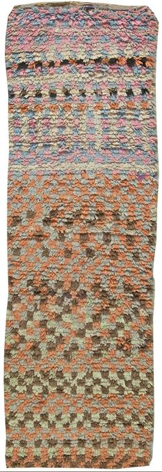 This circa-1945 vintage Moroccan runner rug features a bold raised pile multicolored all-over geometric design that shifts from soft pastel hues in pink and lilac to autumnal oranges and browns. Whether used to connect adjacent rooms or to decorate narrow spaces, the vintage runner carpet is a striking modernist statement. Moroccan rugs have typically been woven by tribal peoples for their utility rather than for decoration. These vintage carpets experienced a growth in popularity in the…