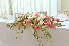 Long and low spray design for the top table with pink roses