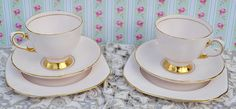 Vintage bone china pair of tea trios made by English china company Tuscan, likely manufacture date 1950s. Trios consists of two tea cups, saucers and large tea plates. The china has a pale pink background decorated with a fine line of gilding around the edges of the china, a fine line on the interior of the cup and around central well of the sauce and plater, handle of the cup and rich gilding to the foot of the cup. The rims of the cup and saucer are gently scalloped, the plate is a curved…