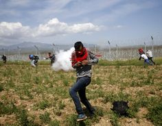 A migrant flees from teargas smoke thrown by Macedonian police on a crowd of more than 500 refugees and migrants protesting next to a border fence at a makeshift camp at the Greek-Macedonian border near the village of Idomeni