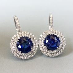18k white gold earrings featuring blue sapphires, accented with diamonds. #doublehalo #bluesapphire #earrings