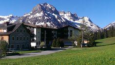 Blick auf das Hotel Goldener Berg und den Alten Goldenen Berg. Saftig grüne Wiesen im Vordergrund und im Hintergrund unser Hausberg Omeshorn noch leicht mit Schnee bedeckt. #Sommer #Arlberg #Bergwelt #goldenerberg #oberlech