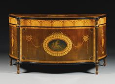 A George III harewood, marquetry and ebonised commode circa 1770, attributed to Mayhew and Ince the serpentine shaped top with a central, garlanded paterae, flanked by further rosettes, within a bowed rosette border and tulipwood banded and ebonised moulded edge, above an arcaded anthemia inlaid frieze on a satinwood ground, the serpentine  front inset with a painted panel within a marquetry surround, between turned, fluted and guilloche carved tapering upright