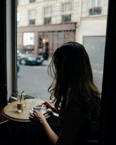 {open} Rowana sits alone in the cafe next to her family's bakery, she watches the people walk in and out.