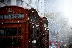 cherry red telephone booth in London covered by snow flurries