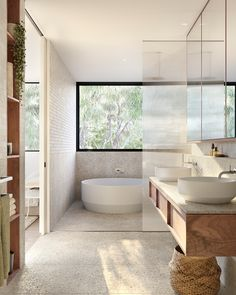 White round solid surface freestanding bathtub with wall mounted bath spout and mixer set Round above counter solid surface basin vessel on wall hung timber vanity with s.