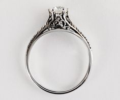 This 1920s white gold diamond engagement ring has beautiful filigree and crisp etching. If she is looking for a gorgeous solitaire but likes