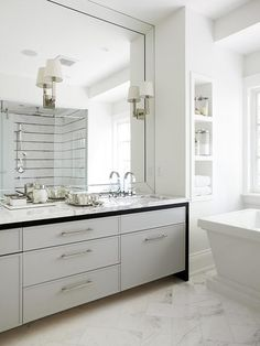 White and gray bathroom features a gray dual washstand topped with white marble fitted with his and hers sinks and modern nickel faucets under a full length beveled mirror lined with sconces.