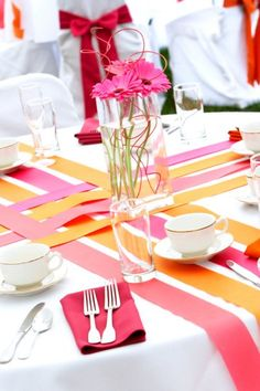Unique way of dressing your wedding table...bright pink and orange with gerber daisy!