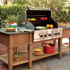 A custom teak island, lit by two low-voltage lamps, holds a drop-in grill and a shelf that keeps extra plates and cooking utensils right where they're needed. | Photo: Deborah Whitlaw Llewellyn | thisoldhouse.com