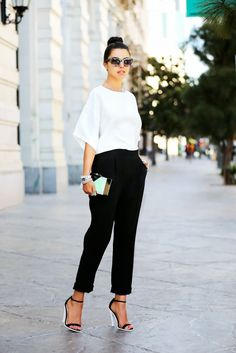 A white blouse is tucked into cropped black pants, and paired with black and white strappy heels, a metallic clutch, and tortoiseshell sunglasses