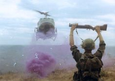 A soldier carrying a M79 grenade launcher giving signals to a Huey in a purple smoke marked LZ.
